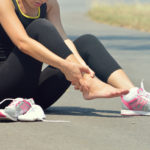 Foot Pain: Young woman suffering from an ankle injury while exercising and running