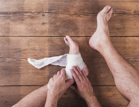 Foot Pain: Injured athlete sitting on a wooden floor