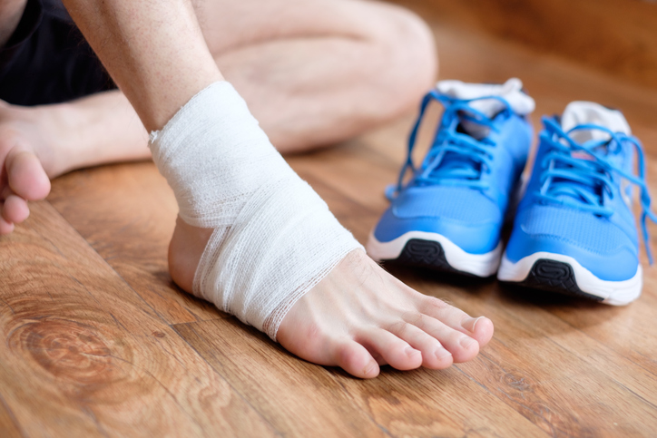 Children Sports Injuries - sportsman massaging his injured ankle after a sport accident