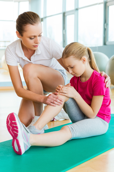 Children Sports Injuries - Woman comforting little girl on floor who hurt her knee