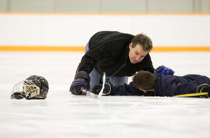 Children Sports Injuries - Hockey player down on the ice