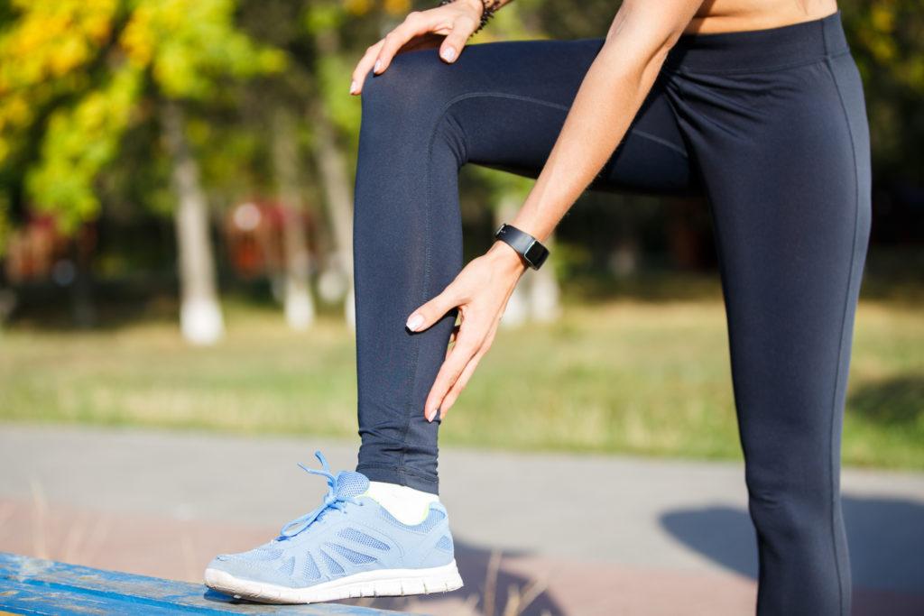 Female runner touching cramped calf at morning jogging. Achilles tendon pain or injury.