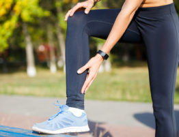 Female runner touching cramped calf at morning jogging. Achilles tendon pain or injury.